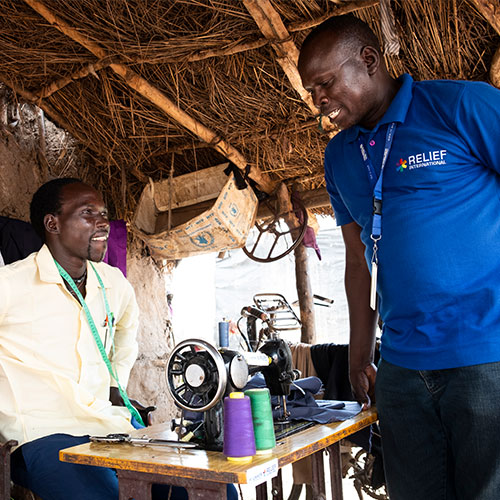Relief International project officer Yones Simon (right) visits Sebit Anguk, 24, a member of a Village Savings and Loan Association (VSLA) in Batil refugee camp, South Sudan. Elie Gardner/RI