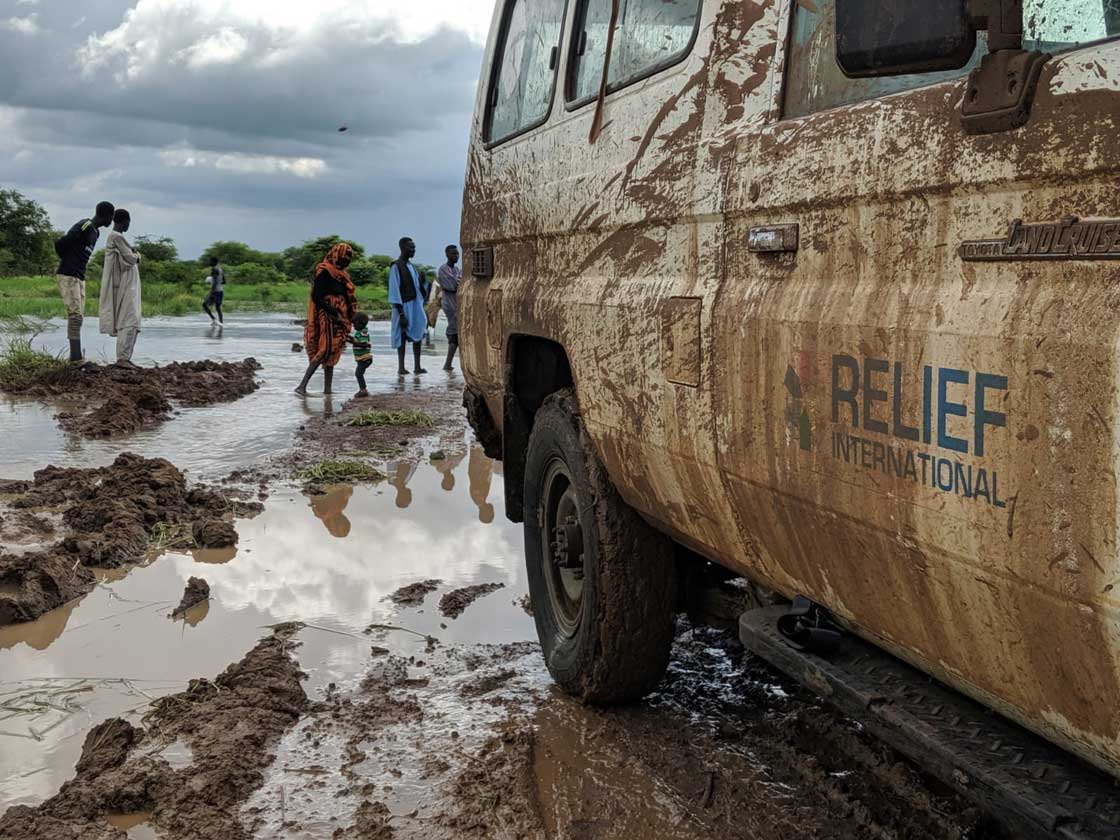 Relief International's team traverses a flooded dirt road in northeastern South Sudan to get to a clinic in a remote community. Elie Gardner/RI
