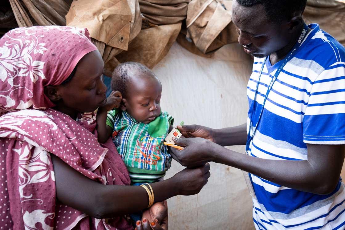 A nutrition assistant at Gentil Hospital confirms Abdul Aziz, 1, is malnourished by measuring his arm. Elie Gardner/RI