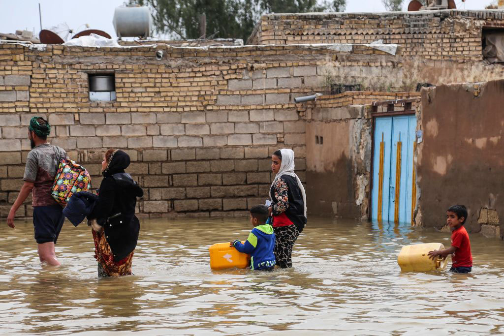 An Iranian family walks through a flooded street in a village around the city of Ahvaz, in Iran's Khuzestan province, on March 31, 2019. Mehdi Pedramkhoo/AFP/Getty Images