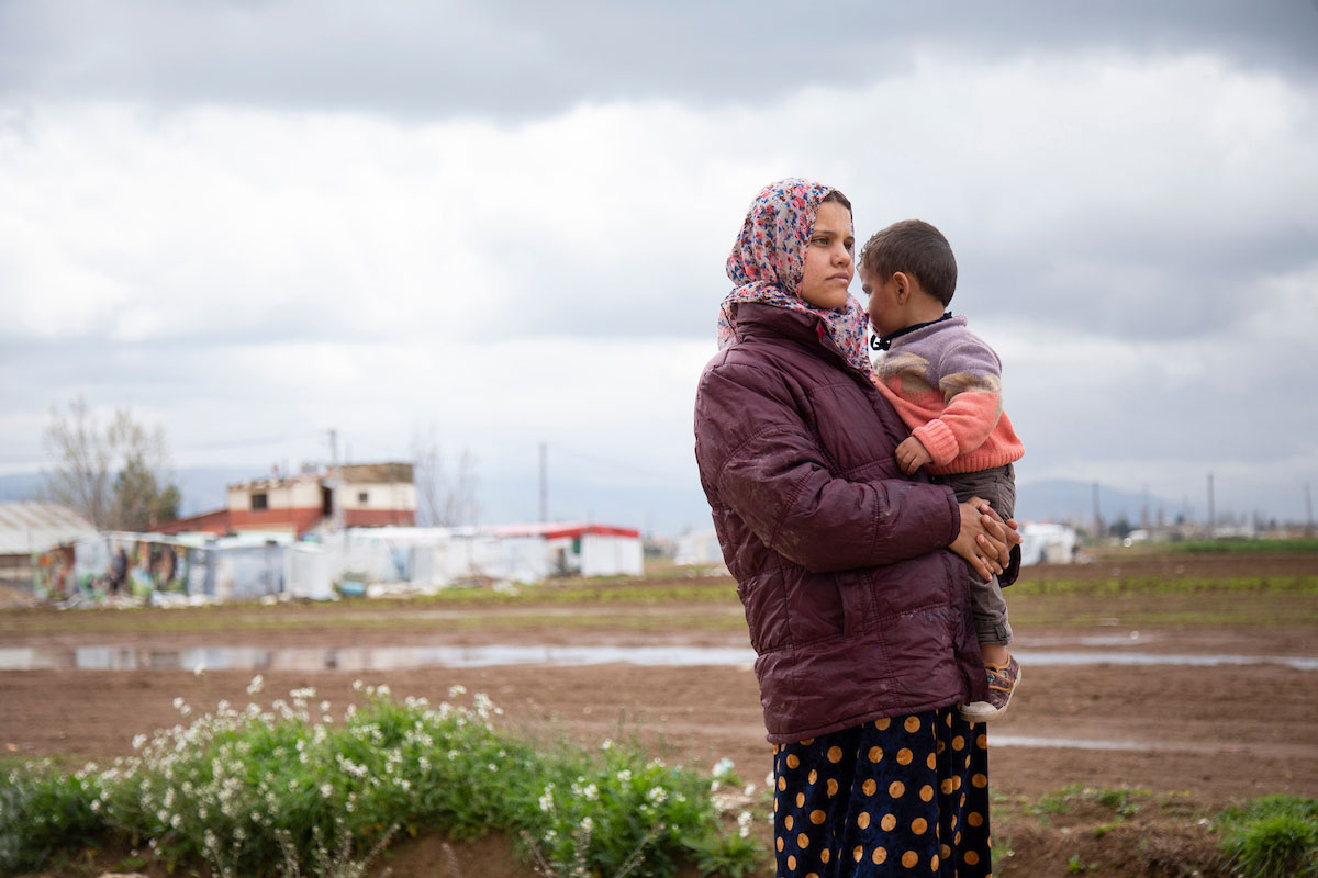 Randa holds her son Jasem, 2, in front of her makeshift shelter in Bekaa Valley, Lebanon. Elie Gardner/RI