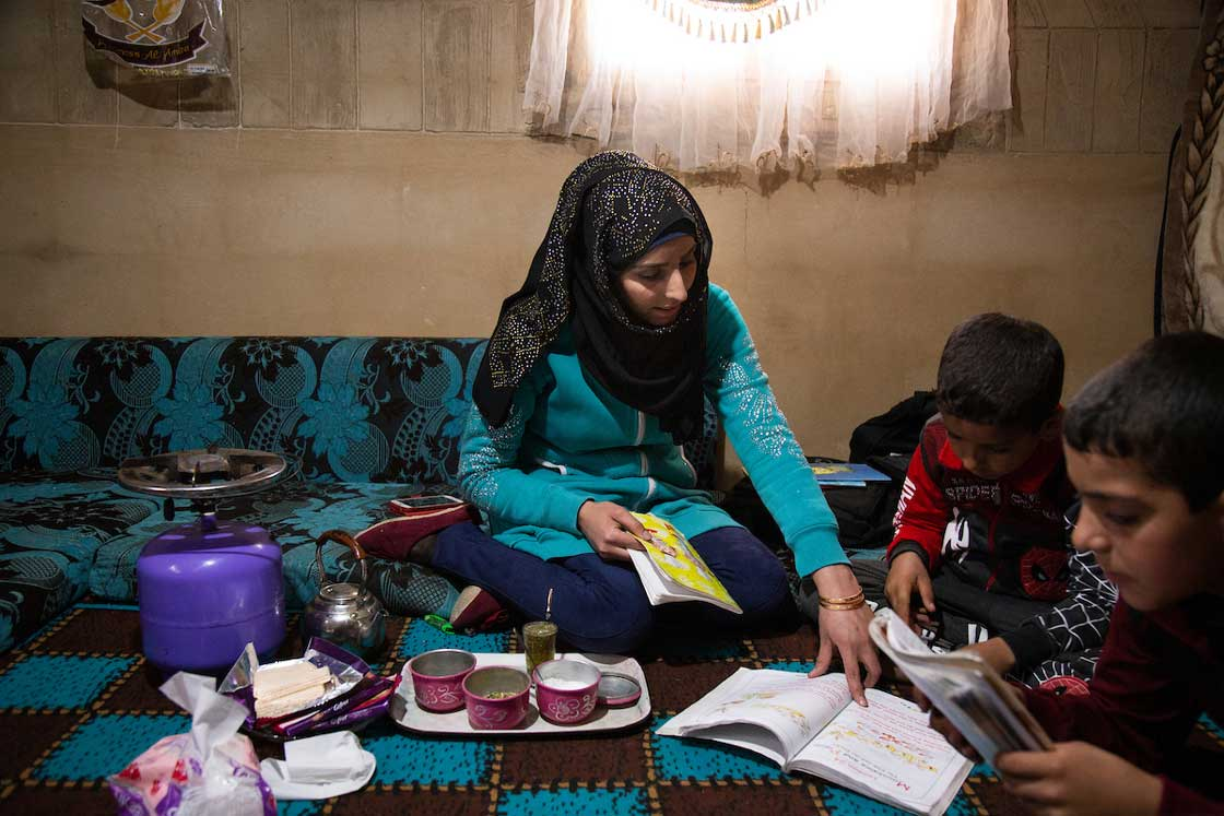 Iman sits with her children as they complete their homework in the morning. Elie Gardner/RI