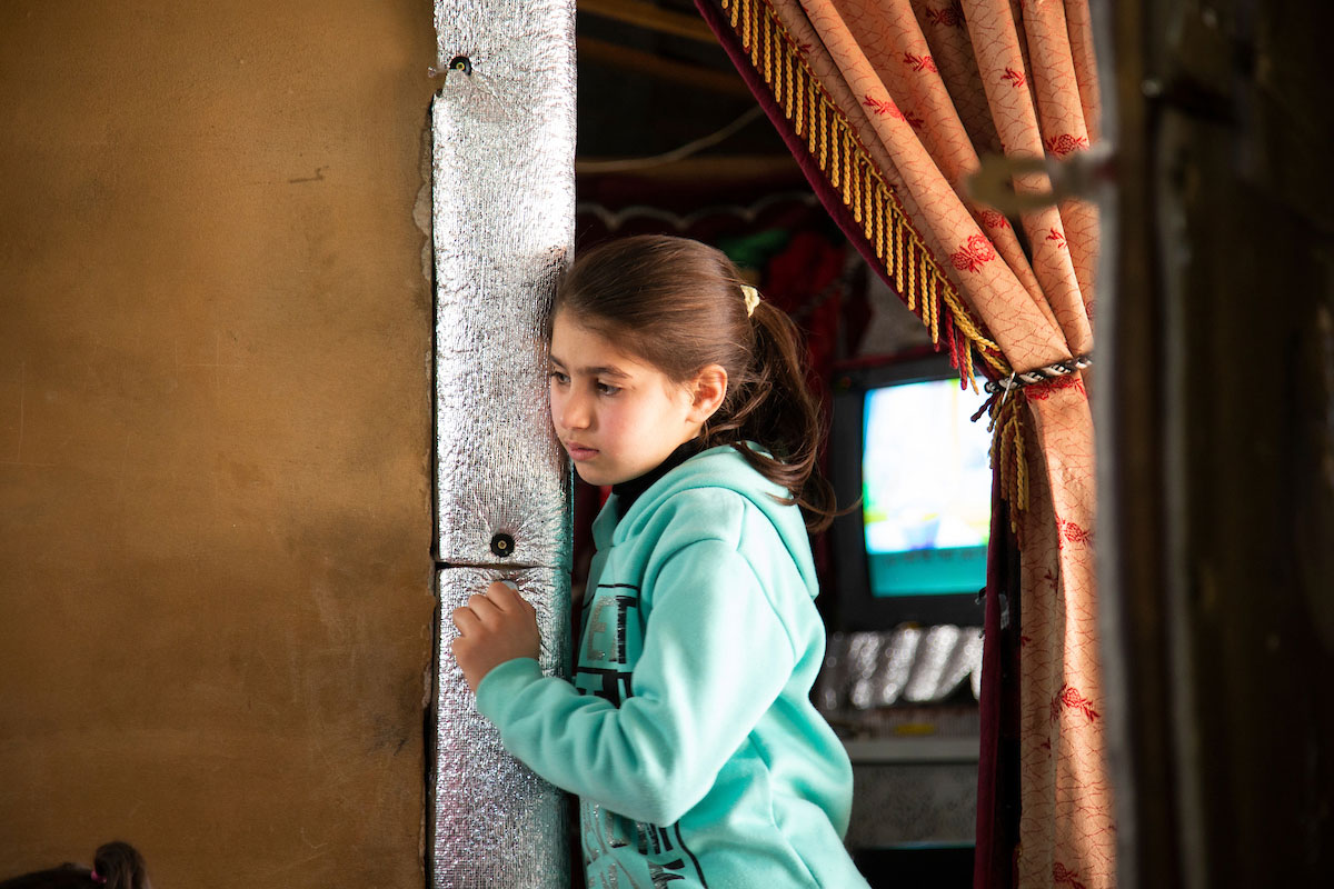 Asmaa's daughter peers around the corner during her mom's psychosocial support session. Elie Gardner/RI