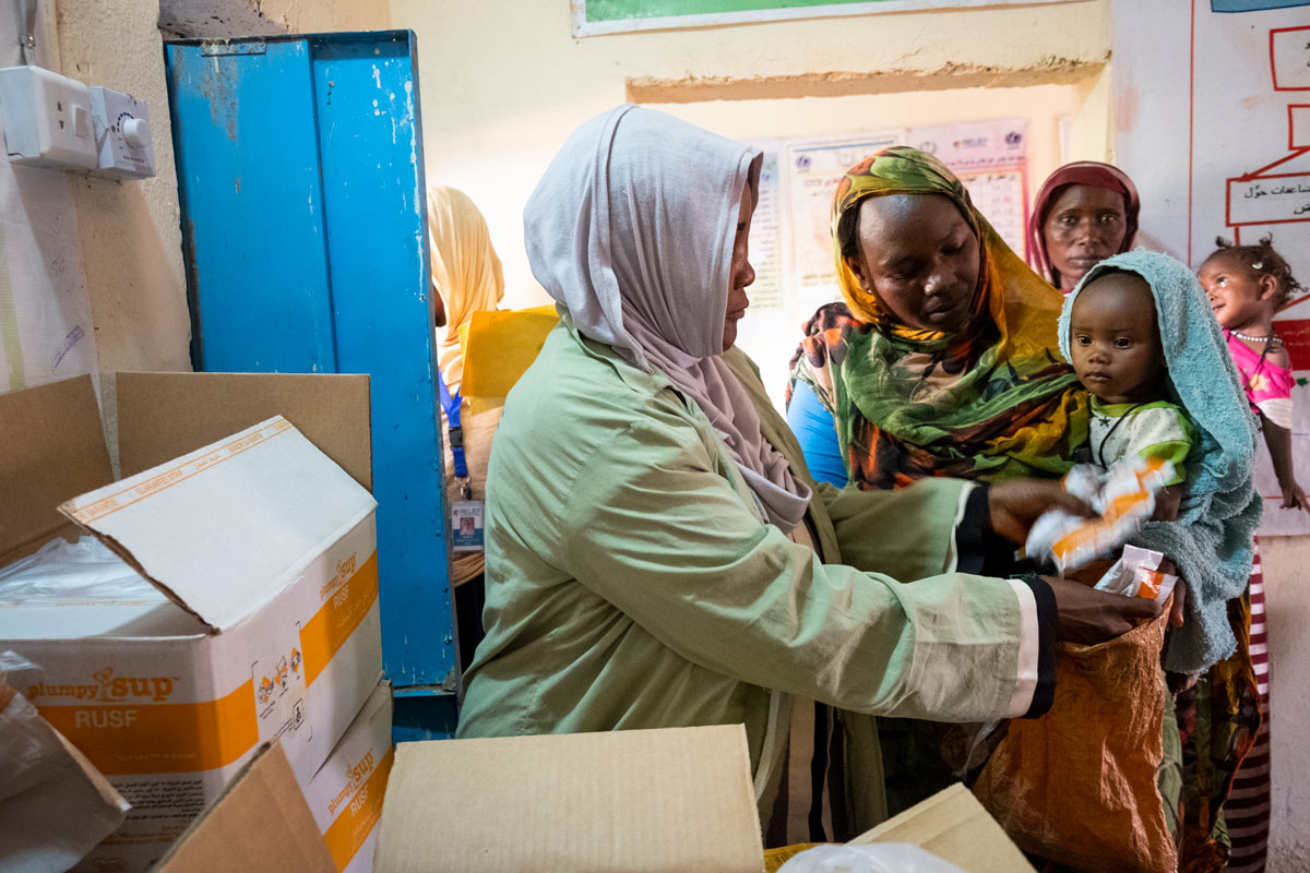 Women line up at Relief International's clinic in Zamzam A during a monthly distribution of Plumpy'Nut, a leading treatment for severe acute malnutrtion.