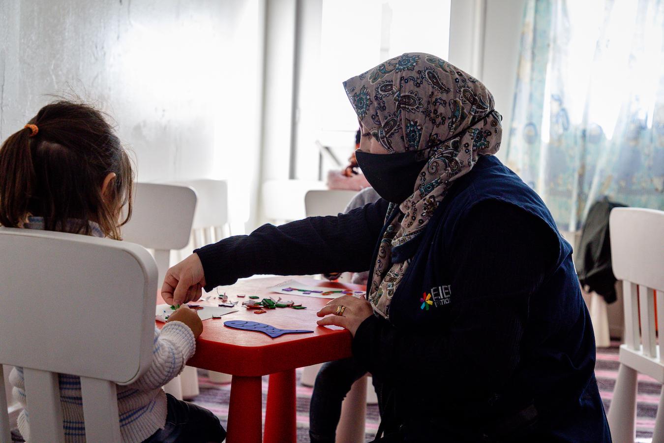 Suzan-teaching-ECD-Azraq-Camp-center-children-Arabic-letters-and-her-daughter-Sham-next-to-her-11.jpg