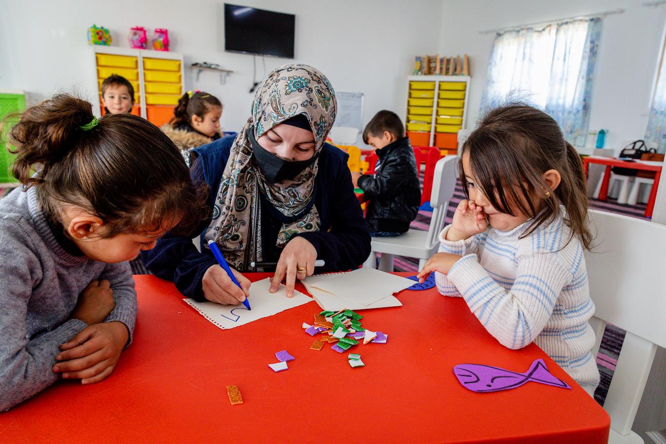 Suzan-teaching-ECD-Azraq-Camp-center-children-Arabic-letters-and-her-daughter-Sham-next-to-her-2.jpg